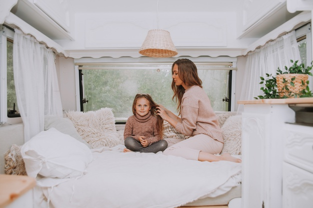 happy-family-mother-little-daughter-relaxing-countryside-inside-white-scandinavian-rustic-camper-van-interior_124463-2801