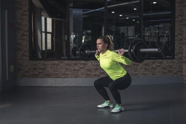 Žena v žltom tričku cvičí s činkami v posilňovni