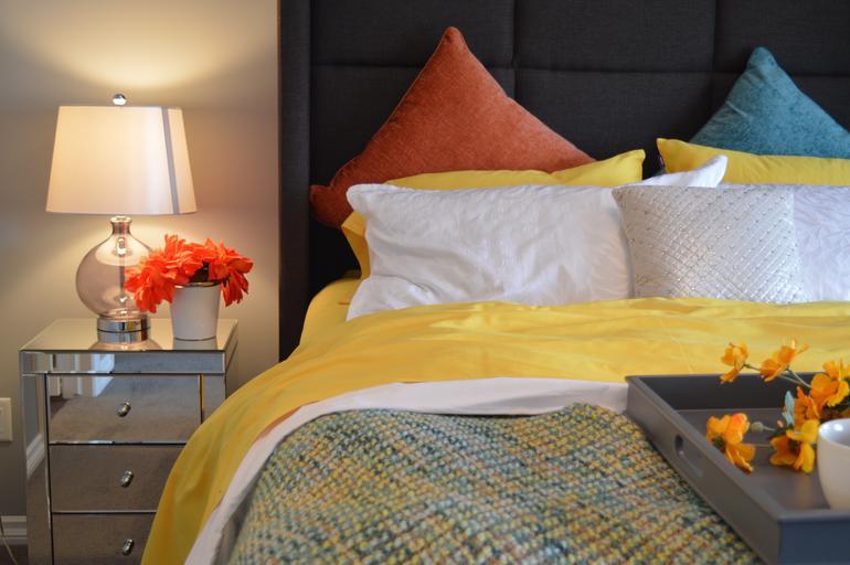 Posteľ so žltou obliečkou, podnosom s raňajkami, bielymi, oranžovými a modrými vankúšmi