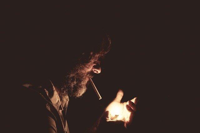 Zanedbaný muž si zapaľuje cigaretu v tme.jpg