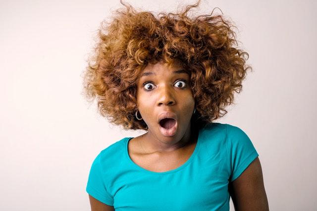 Žena s kučeravými vlasmi sa tvári prekvapene